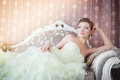 Beautiful bride sits on the couch in a wedding dress sofa in interior Royalty Free Stock Photo