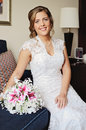 Beautiful bride sitting on couch with her bouquet Royalty Free Stock Photos