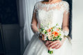 A beautiful bride is standing near the window and holding a wedding bouquet with white roses and peach peonies. Close-up Royalty Free Stock Photo