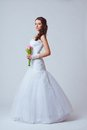 Beautiful bride studio full length portrait holding bouquet toned image Stock Images