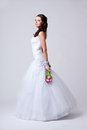 Beautiful bride studio full length portrait holding bouquet and turned sideways Stock Photography
