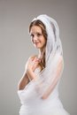 Beautiful bride with veil portrait of isolated over gray background Royalty Free Stock Image