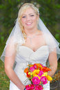 Beautiful bride in white dress wedding holding a colorful bouquet of flowers Stock Photos