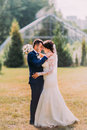 Beautiful bride with white wedding dress and groom in stylish blue suit kissing outdoor on lawn. Greenhouse at Royalty Free Stock Photo