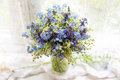 Beautiful bright blue and white bouquet with wild flowers on windowsill in sunlight . Closeup photo with bokeh Royalty Free Stock Photo