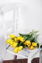 Beautiful bright yellow tulips in still life lying on antique white chair bouquet of for your favorite a room Stock Photo