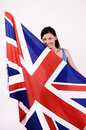 Beautiful British girl smiling holding up the UK flag. Stock Image
