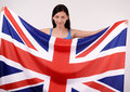 Beautiful British girl smiling holding up the UK flag. Royalty Free Stock Images