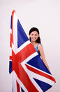 Beautiful British girl smiling holding up the UK flag looking away. Royalty Free Stock Photography