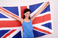 Beautiful british girl smiling holding up the uk flag young woman standing with in back Stock Images