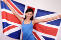 Beautiful british girl smiling holding up the uk flag young woman standing with in back Stock Photos