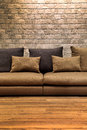 Beautiful brown fabric sofa on wooden floor with brick wall Royalty Free Stock Photo
