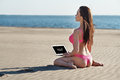 Beautiful brunette on the beach on a hot summer day in pink lingerie sitting holding laptop Stock Photo