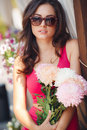 Beautiful brunette with a bouquet of pink flowers Royalty Free Stock Photo