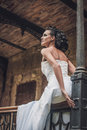 Beautiful brunette bride in a wedding dress sitting on railing photo Royalty Free Stock Photography
