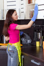 Beautiful brunette cleans the kitchen furniture Royalty Free Stock Photo