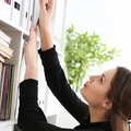 Beautiful brunette female clerk searching for proper document Royalty Free Stock Photo