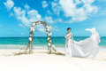 Beautiful brunette fiancee in white wedding dress with big long train and bouquet stand on shore sea near the Royalty Free Stock Image