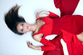 Beautiful brunette girl attractive woman posing in red dress looking at camera lying Stock Photo