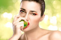 Beautiful brunette girl biting an apple young woman a green closeup portrait Stock Photos