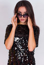Beautiful brunette girl in a black dress and sunglasses. Brunette with long black hair Royalty Free Stock Photo