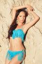 Beautiful brunette girl in blue bikini posing near sand wall Royalty Free Stock Image