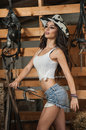 Beautiful brunette girl with country look, indoors shot in stable, rustic style. Attractive woman with cowboy hat, denim shorts Royalty Free Stock Photo