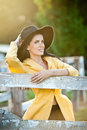 Beautiful brunette girl with country look near an old wooden fence. Attractive woman with black hat and yellow coat Royalty Free Stock Photo
