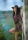 Beautiful brunette girl with country look, outdoors shot near wooden fence, rustic style. Attractive woman with cowboy hat Royalty Free Stock Photo