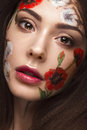 Beautiful brunette girl with curls and a floral pattern on the face. Beauty flowers. Royalty Free Stock Photo