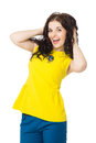 Beautiful brunette girl with curly hair wearing yellow blouse happy and blue pants over white background Royalty Free Stock Image