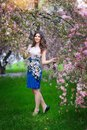 Beautiful brunette girl in the flowered garden Royalty Free Stock Images