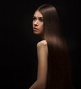 Beautiful brunette girl with healthy long hair on dark background Royalty Free Stock Photo