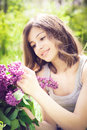 Beautiful brunette girl with a lilac flowers relaxing and enjoying life in nature outdoor shot copyspace Stock Photos