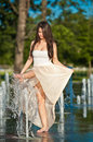 Beautiful brunette girl playing at  water fountain Stock Photography