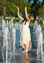 Beautiful brunette girl playing at  water fountain Stock Photo