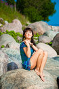 Beautiful brunette girl sitting on beach stones Stock Photography