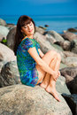 Beautiful brunette girl sitting on beach stones Royalty Free Stock Photos