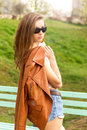 Beautiful brunette girl in sunglasses with a jacket stands in the park Stock Photos