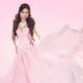 Beautiful brunette girl wearing in wedding dress isolated on pin pink background Royalty Free Stock Image
