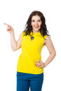 Beautiful brunette happy girl with curly hair pointing with fin wearing yellow blouse and blue pants over white background Royalty Free Stock Photos