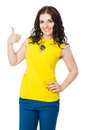 Beautiful brunette happy girl with curly hair thumbs up wearing yellow blouse and blue pants over white background Stock Photo