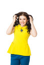 Beautiful brunette happy girl with curly hair wearing yellow bl blouse and blue pants over white background Stock Image