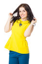 Beautiful brunette happy girl with curly hair wearing yellow bl blouse and blue pants over white background Stock Photos