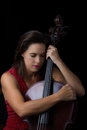 Beautiful brunette holding cello with selective light in red dre a dress Royalty Free Stock Images