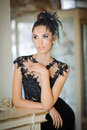 Beautiful brunette lady in elegant black lace dress posing in a vintage scene. Young sensual fashionable woman Royalty Free Stock Photo