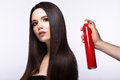 Beautiful brunette model with classic makeup and bottle of hair products. beauty face. Royalty Free Stock Photo
