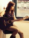 Beautiful brunette playing acoustic guitar Royalty Free Stock Image