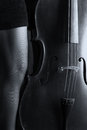 Beautiful brunette playing cello with selective light in black d
