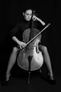 Beautiful brunette playing a cello with selective light in black